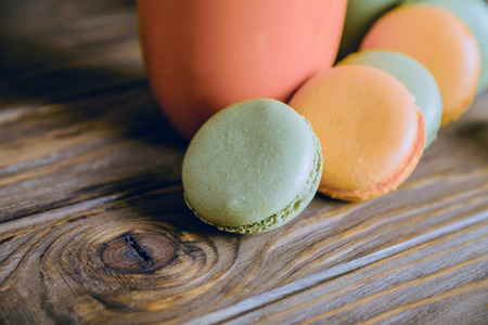 dark pastel green: Close view at orange and green french pistachios and orange macaroons in dark colors on a wooden background. Pastel colors. Shallow depth of field. Focus at first macaroon.
