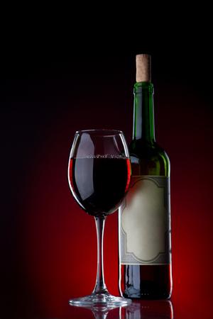 copa de vino: De vino de vidrio contra un fondo negro con la luz roja con la reflexi�n sobre un fondo. Fous en un vaso
