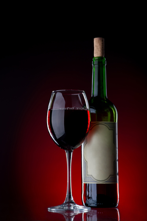 wine colour: Wine and glass against a black background with red light with reflection on a bottom. Fous on a glass