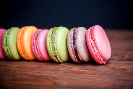 pale colors: French, raspberry pistachios and orange macaroons standing in a row in dark colors on a wooden background. Shallow depth of field. First macaroons in focus. Vintage pale colors