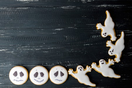 holiday cookies: Halloween homemade gingerbread cookies with different ghosts over wooden black table