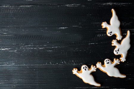 Halloween homemade gingerbread cookies with ghosts over wooden black table Stock Photo - 47319442