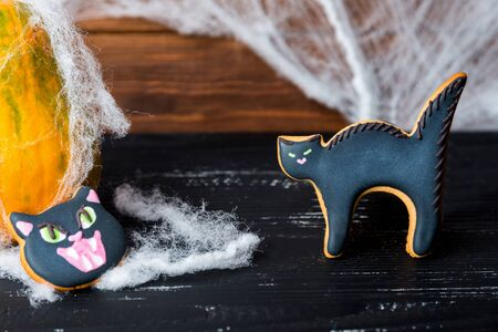 pumkin: Close view at homemade halloween sweets gingerbread cookies  cat head and cat over black wooden table with pumkin on a back and spiderweb. Stock Photo