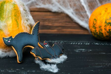 pumkin: Close view at homemade halloween sweets gingerbread cookies  cat. and bat over black wooden table with pumkin on a back and spiderweb. Shallow depth of field.