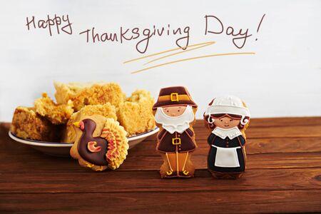 thanksgiving day symbol: Ringraziamento card Felice. Vista vicina a figure di pellegrini pan di zenzero con Ringraziamento torta di zucca su una schiena su uno sfondo di legno. Con il segno.