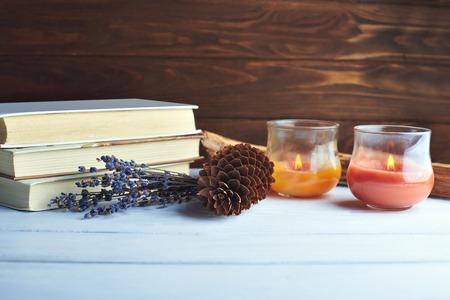 candela: Still life di accessori inverno. pigna, candele, libri, profumo di lavanda su uno sfondo di legno nei colori rosa-viola d'epoca Archivio Fotografico