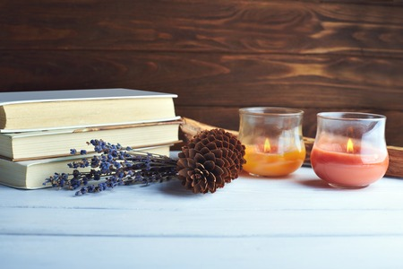 candle: Still life of winter accessory. Pine cone, candles, books, bouquet lavender on a wooden background in vintage pink-violet colors
