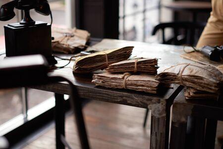 cartas antiguas: El manojo de cartas viejas tided con cordones, teléfono antiguo y prismáticos sobre un borde de la mesa de metal. Con el primer plano borrosa.