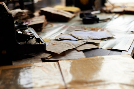 View on a desk in a old military office. A stack of old letters tied with laces, typewriter old yellow paper, binoculars, ash tray lying on a map, telephone.  Shallow depth of field.