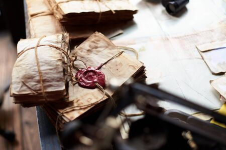 old letters: A stack of old letters tied with laces on yellow paper with a red wax seal on the table with blurry foreground