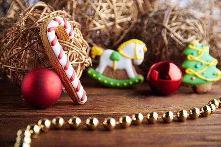 angel tree: Christmas mood still life with gingerbread horse toy and christmas angel, tree with red christmas balls and gold decoration. With copy space. Focus on a lollypop. Stock Photo