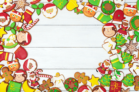 angel cat: Background of christmas gingerbread cookies with christmas figures on white wooden background. Top view.  With copy space in the middle.