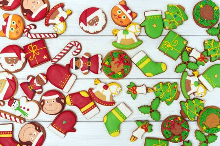 angel cat: Close view at scattered background of christmas red and green gingerbread cookies with christmas figures on white wooden background. Top view.  With copy space on the left Stock Photo