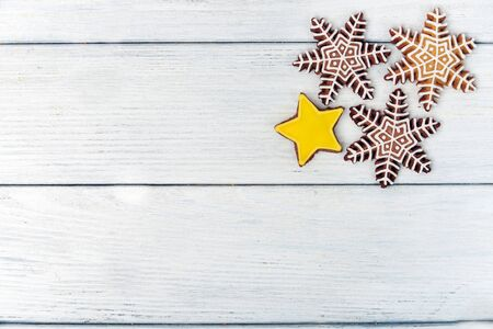 yellow star: Christmas homemade gingerbread snowflake and a yellow star cookie over white wooden table with copy space. Top view. Stock Photo