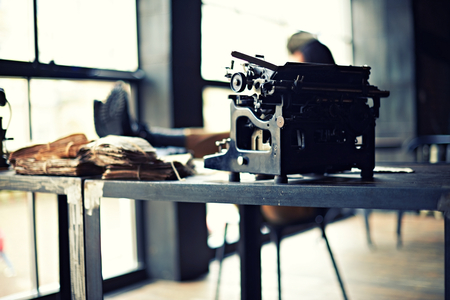hard day at the office: View on a desk in a old military office. A stack of old letters tied with laces, old yellow paper, binoculars, ash tray lying on a map, telephone. With a person holding binoculas Stock Photo