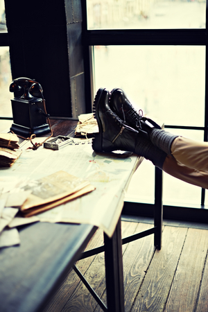 hard day at the office: View on a desk in a old military office. Bunch of old letters tied with laces, old yellow paper, binoculars, telephone and female legs on a map.  Shallow depth of field. Vintage colors. Vertical shot Stock Photo