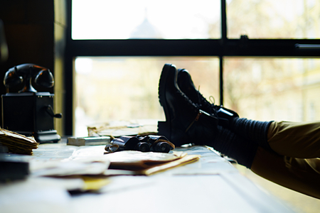 hard day at the office: View on a desk in a old military office. A stack of old letters tied with laces, old yellow paper, binoculars, telephone and female legs.  Shallow depth of field.