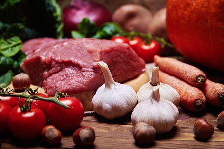 carne asada: Cerrar vista de ajo con variedad de verduras frescas, la carne cruda, las setas y frutos secos sobre una tela de arpillera y un fondo de madera