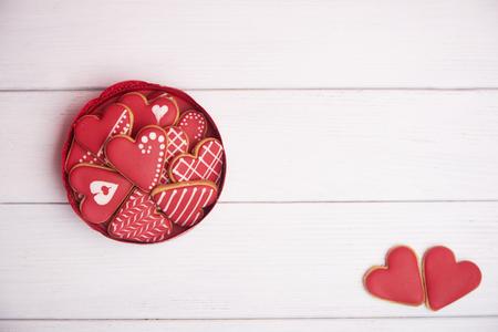 tarjeta de San Valentín. Tres panes de jengibre con forma de corazón sobre fondo de madera rústica. Vista superior.