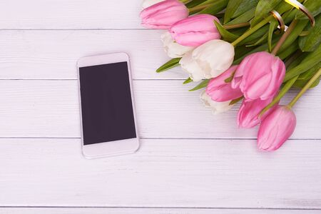 spring flowers: White smartphone with blank screen lying on  turquoise wooden table near spring tulips background