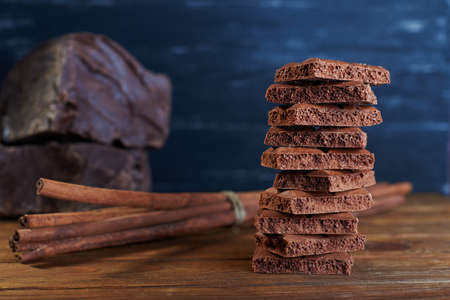 porous: Porous milk chocolate assembled in pyramid with cinnamon and dark chocolate on a back on a wooden dark background. Stock Photo