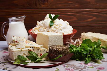 milk products: Set of dairy milk products: milk in glass, soft cream cheese, butter, cheese with spices and mint on old rustic wooden background. Dark rustic style.