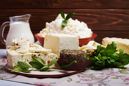 non vegetarian: Set of dairy milk products: milk in glass, soft cream cheese, butter, cheese with spices and mint on old rustic wooden background. Dark rustic style.