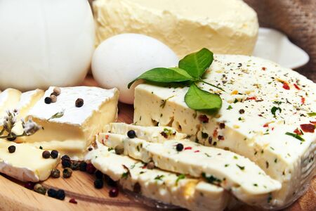 speciality: Close view at delicious array of gourmet cheese on with an assortment of uncut speciality regional cheese,with fresh milk, butter and eggs on a burlap rustic cloth Stock Photo