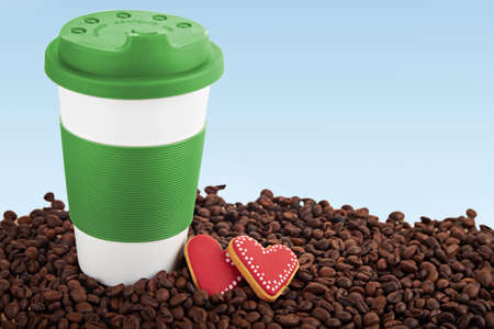scattered in heart shaped: Takeaway green ceramic cup with gingerbread heart shaped cookies. Scattered coffee beans on blue background. Copy space. Focus on cookies Stock Photo