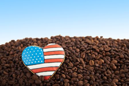 scattered in heart shaped: close view at gingerbread heart shaped cookies with american flag. Scattered coffee beans on blue background. Copy space Stock Photo