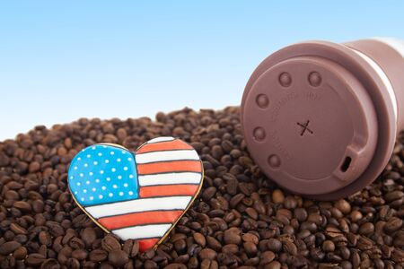 scattered in heart shaped: close view at at takeway brown ceramic cup gingerbread heart shaped cookies with american flag. Scattered coffee beans on blue background. Copy space