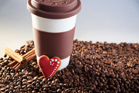 scattered in heart shaped: Takeaway brown ceramic cup with cinnamon and gingerbread heart shaped cookies. Scattered coffee beans on blue background. Copy space. In sunlight rays