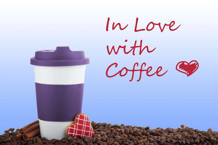 scattered in heart shaped: Takeaway brown ceramic cup with cinnamon and gingerbread heart shaped cookies. Scattered coffee beans on blue background. With sign in love with coffee
