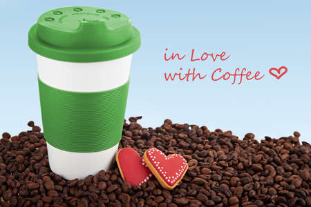 scattered in heart shaped: Takeaway green ceramic cup and gingerbread heart shaped cookies. Scattered coffee beans on blue background. With sign in love with coffee Stock Photo