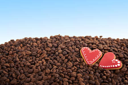 scattered in heart shaped: close view at gingerbread heart shaped cookies. Scattered coffee beans on blue background. Copy space