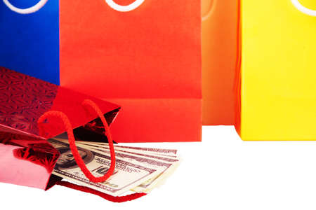 extortion: Close view at red paper bag with United States dollar bills coming out of it for concepts money shopping, cash bussines with other paper bags isolated on a white Stock Photo