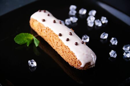 field mint: exquisite cream dessert eclair with fresh mint leaves on a black plate. Shallow depth of field