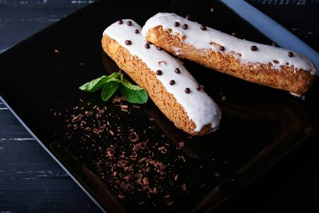 field mint: Two exquisite cream dessert eclair with fresh mint leaves on a black plate. Shallow depth of field Stock Photo
