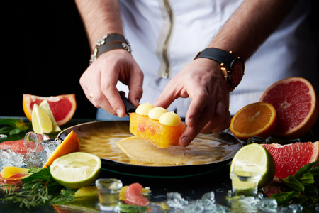 Chef hands putting citrus tart on a plate with a lot of citrus fruits and ice around