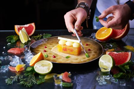 Chef hands putting mint leaves around citrus tart on a plate with a lot of citrus fruits and ice around