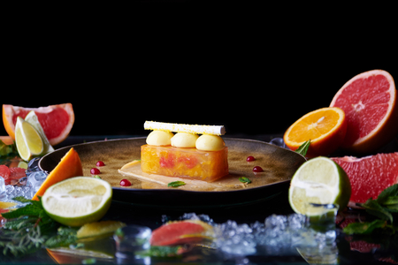 Molecular cuisine. citrus tart on a plate with fruits around