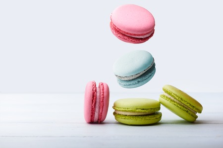 white fly: Different types of macaroons in motion falling on a white wooden background Stock Photo