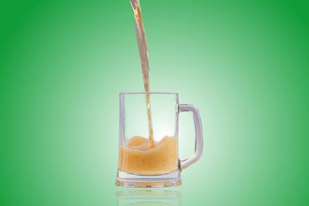 alehouse: Beer pouring into half full glass. With nice big foam and reflection of a glass. Isolated on a green background.