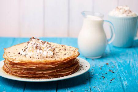 hot cakes: Desayuno con las crepes con crema delicioso dulce en una parte superior y jarra con leche y una taza de café en un fondo de madera azul. Foto de archivo