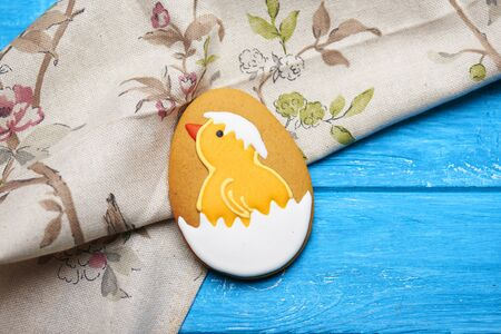easter cookie: Top view at big Easter cookie with icing. Chicken in the egg. Napkin on a blue wooden backgroud Stock Photo
