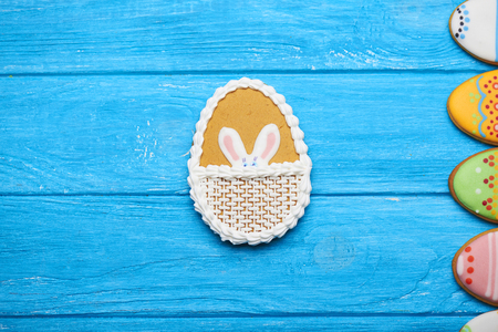middle easter: Delicious Easter cookies background. Big Easter cookie with rabbits ears in the middle and a half of eggs cookie on a blue wooden background. Top view.
