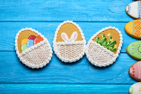 middle easter: Delicious Easter cookies background. Three big Easter cookies with rabbits ears, flowers and eggs in the middle and a half of eggs cookie on a blue wooden background. Top view. Stock Photo