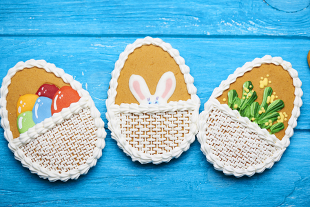 middle easter: Delicious Easter cookies background. Three big Easter cookies with rabbits ears, flowers and eggs in the middle on a blue wooden background. Top view.