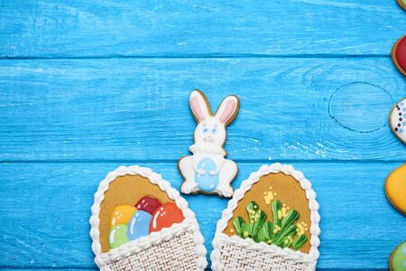 middle easter: Delicious Easter cookies background. Two big Easter cookies with flowers and eggs on a basket and a cookie rabbit in the middle and a half of eggs cookie on a blue wooden background. Top view.