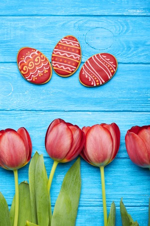 verticals: Easter cookies background. Red tulips at the bottom, rred Easter eggs on a blue wooden background. Top view. Verticals shot Stock Photo